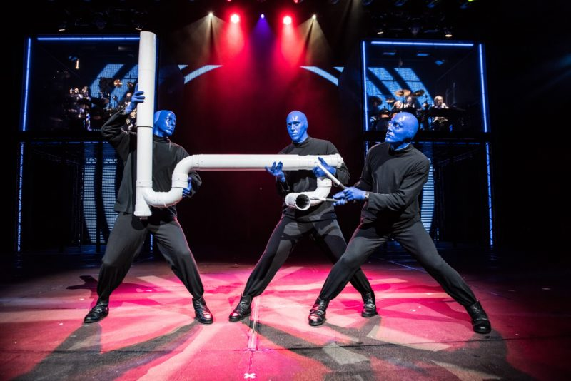 3 men dressed in black with blue skin hold a large pipe