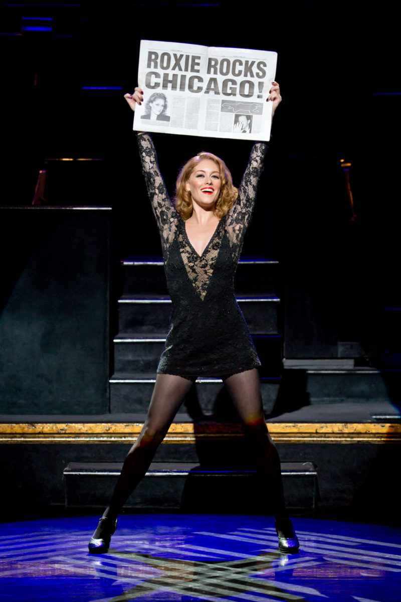 "The actress playing Roxie Hart in CHICAGO strikes a pose holding a newspaper above her head with the headline ""ROXIE ROCKS CHICAGO"" in a moment from the song ""Roxie."""