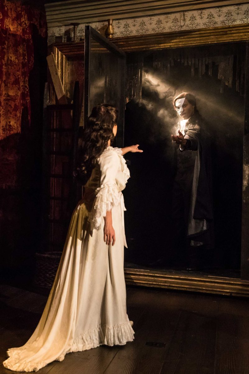 The Phantom of the Opera appears to Christine inside a mirror replacing her own reflection. He beckons her to join him.